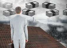 Money icons and Businessman standing on Roof with chimney and misty city Stock Images