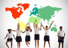 Multicultural Kids jumping in front of colorful world map Stock Photos