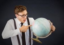 Nerd man pointing at globe against navy chalkboard Royalty Free Stock Photo