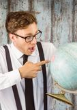 Nerd man pointing at globe against wood panel Royalty Free Stock Image