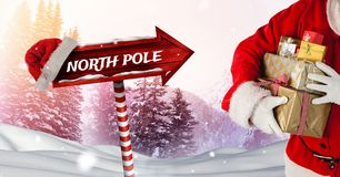 North Pole text and Santa holding gifts with Wooden signpost in Christmas Winter landscape and Santa. Digital composite of North Pole text and Santa holding Stock Photography