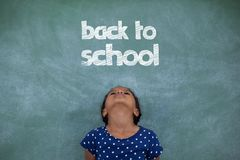 Office kid girl looking up against green background with back to school text Stock Images
