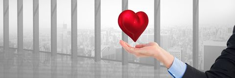 Open hand and heart over city window by office window. Digital composite of open hand and heart over city window by office window Stock Photography