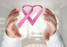 Open hands with pink ribbon for breast cancer awareness Stock Photo