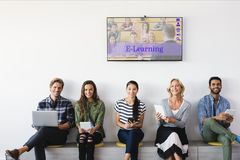 People sitting under a TV with e-learning information in the screen. Digital composite of People sitting under a TV with e-learning information in the screen Stock Photography