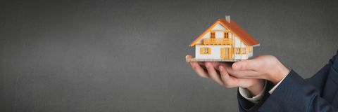 Person holding a house against grey background as house insurance concept. Digital composite of Person holding a house against grey background as house insurance Royalty Free Stock Photo
