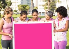Pink breast cancer awareness women holding card. Digital composite of pink breast cancer awareness women holding card royalty free stock image