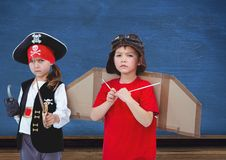 Pirate girl and pilot boy in front of blue wall. Digital composite of Pirate girl and pilot boy in front of blue wall Stock Image