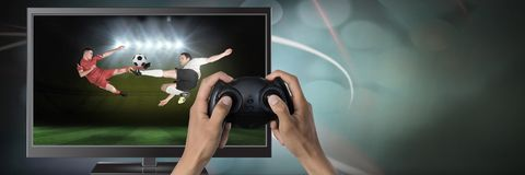 Playing soccer computer game with controller in hands. Digital composite of Playing soccer computer game with controller in hands stock image