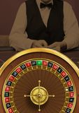 Roulette wheel and croupier in casino. Digital composite of Roulette wheel and croupier in casino royalty free stock photo