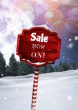 Sale now on text on Wooden signpost in Christmas Winter landscape. Digital composite of Sale now on text on Wooden signpost in Christmas Winter landscape Stock Photography