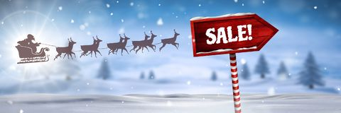 Sale text on Wooden signpost in Christmas Winter landscape and Santa`s sleigh and reindeer`s. Digital composite of Sale text on Wooden signpost in Christmas Stock Photo
