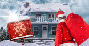 Santa Claus looking at  3d winter scenery with house Royalty Free Stock Images