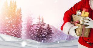Santa holding gifts in Christmas Winter landscape. Digital composite of Santa holding gifts in Christmas Winter landscape Stock Photo