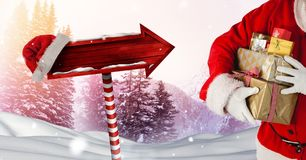 Santa holding gifts and Wooden signpost in Christmas Winter landscape and Santa hat. Digital composite of Santa holding gifts and Wooden signpost in Christmas Stock Images