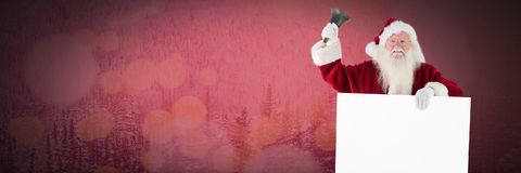 Santa holding a white card and phone Royalty Free Stock Photos
