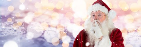 Santa with Winter landscape gesturing to be quiet. Digital composite of Santa with Winter landscape gesturing to be quiet Royalty Free Stock Photo