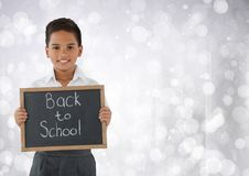 Schoolboy holding back to school blackboard in front of bright bokeh background Royalty Free Stock Photography