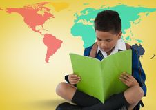 Schoolboy reading in front of colorful world map. Digital composite of Schoolboy reading in front of colorful world map Stock Photo