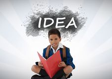 Schoolboy reading under idea text. Digital composite of Schoolboy reading under idea text Royalty Free Stock Photography