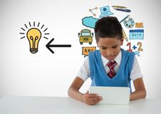 Schoolboy on tablet with education light bulb graphics. Digital composite of Schoolboy on tablet with education light bulb graphics Stock Images