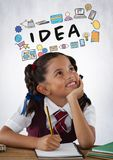 Schoolgirl writing at desk with idea graphics Royalty Free Stock Photos