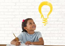 Schoolgirl writing at desk with light bulb Stock Photography