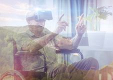 Senior man on wheelchair with VR glasses in the mountains. Digital composite of senior man on wheelchair with VR glasses in the mountains Stock Image