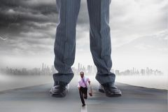 Small business man running from a big business man. Digital composite of Small business men running from a big business man royalty free stock photos
