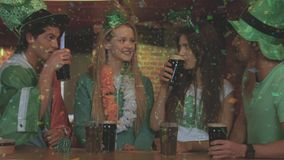 Digital composite of smiling friends with Irish accessory in the bar. Against illustration of confetti vector illustration
