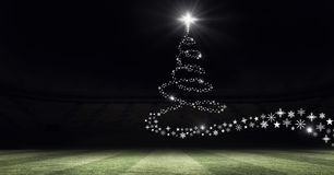 Snowflake Christmas tree pattern shape glowing on sports field stadium. Digital composite of Snowflake Christmas tree pattern shape glowing on sports field Royalty Free Stock Images