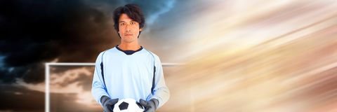 Soccer goalkeeper holding football in goal with transition stock photography
