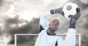 Soccer goalkeeper saving football in goal. Digital composite of Soccer goalkeeper saving football in goal royalty free stock images