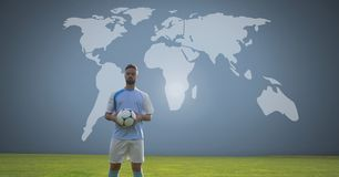 Soccer player holding football with world map stock photography