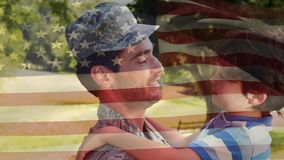 Soldier carrying his son. Digital composite of a soldier talking to his son while carrying him in his arms with an American flag waving in the foreground stock video