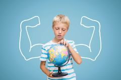 Student boy with fists graphic holding a globe against blue background Stock Images