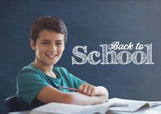 Student boy at table against blue blackboard with back to school text. Digital composite of Student boy at table against blue blackboard with back to school text Royalty Free Stock Photography