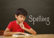 Student boy at table against grey blackboard with spelling text. Digital composite of Student boy at table against grey blackboard with spelling text Royalty Free Stock Image