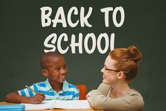 Student boy and teacher at table against green blackboard with back to school text Stock Photography