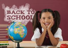 Student girl at table against red blackboard with back to school text Royalty Free Stock Images