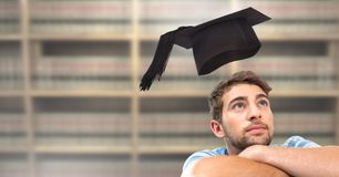 Student man in education library with graduation hat. Digital composite of Student man in education library with graduation hat stock photography
