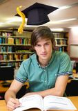 Student man in education library with graduation hat. Digital composite of Student man in education library with graduation hat stock images