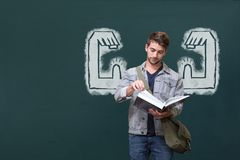Student man with fists graphic reading against green blackboard Stock Photography