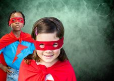 Superhero kids in front of green background. Digital composite of Superhero kids in front of green background stock images