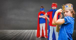 Superhero kids and king crown boy with blackboard background. Digital composite of Superhero kids and king crown boy with blackboard background Royalty Free Stock Photography