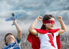 Superhero kids playing with toy plane over city royalty free stock photography