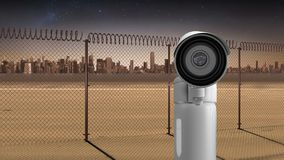 Surveillance camera. Digital composite of surveillance camera moving and background shows a field with barricade stock illustration