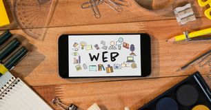 Table top with a phone with web graphics on the screen Stock Images