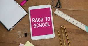 Tablet on a school table with back to school on screen Royalty Free Stock Photo