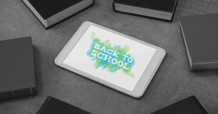 Tablet on a school table with back to school text on screen Stock Image